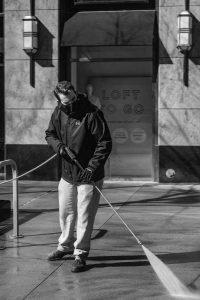 Man making money pressure washing sidewalk